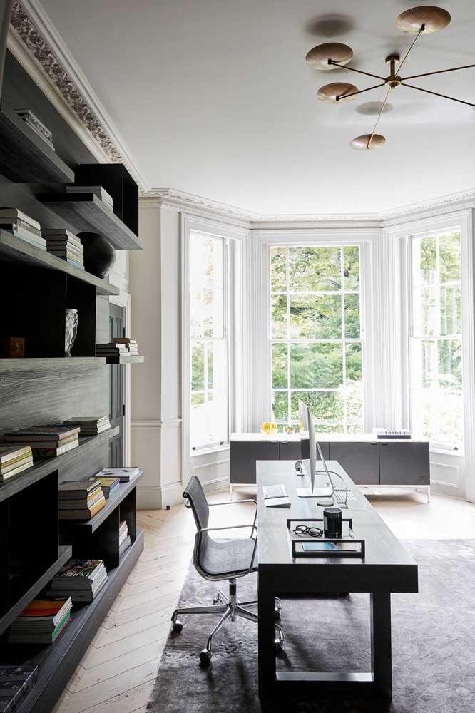 O Home Oficce sóbrio e elegante traz aos fundos uma ampla Bay Window para ampliar e iluminar o espaço
