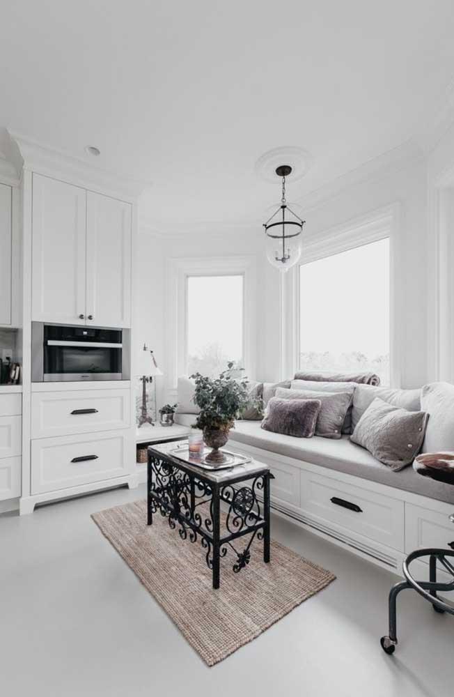 A cozinha branca e clean ficou super aconchegante com a Bay Window acompanhada do sofá cheio de almofadas