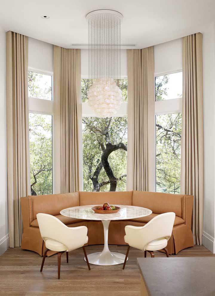 Tudo aqui parece ter sido feito um para o outro: a cortina, a Bay Window, o canto alemão com mesa de jantar, o lustre pendente e, claro, o visual marcante que entra pela janela