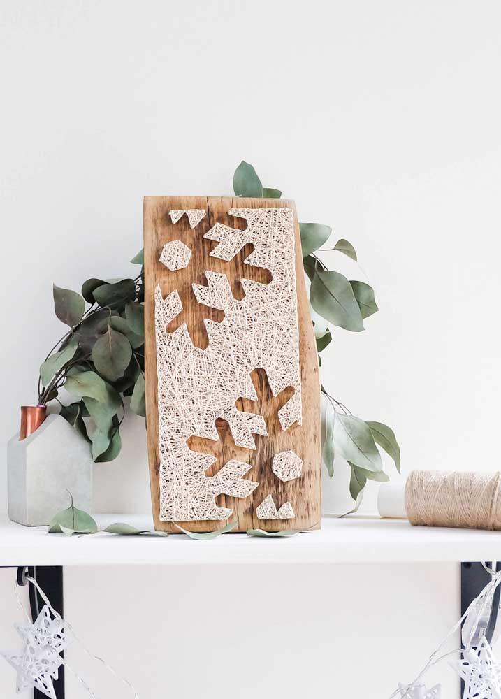 Esse painel em madeira também trouxe o String Art perfeito para decorar o Natal, com flocos de neve vazados