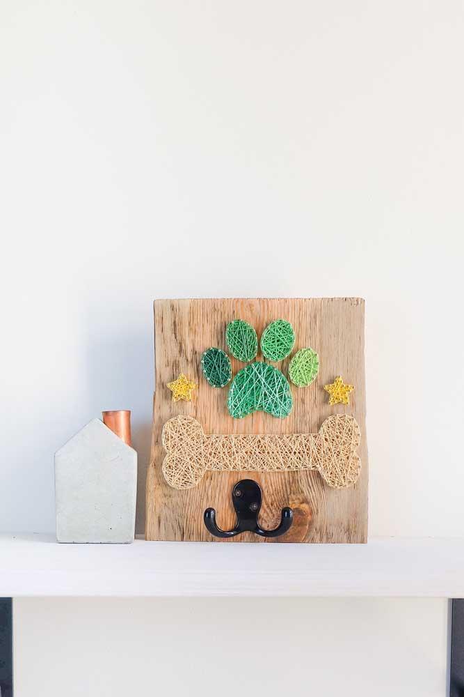 Que fofo! Esse String Art foi dedicado a quem ama pets; repare que a base em madeira traz um gancho, tornando a arte funcional também