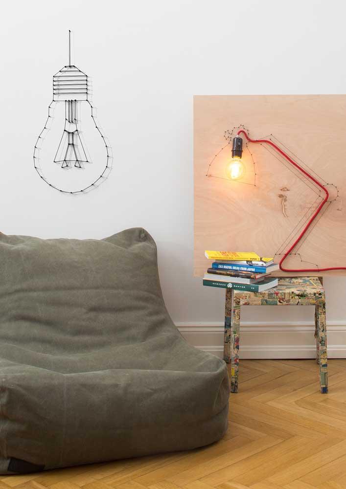 Muito criativo, esse String Art forma o desenho de uma lâmpada na parede da sala de estar; ao lado, o String Art contorna a luminária
