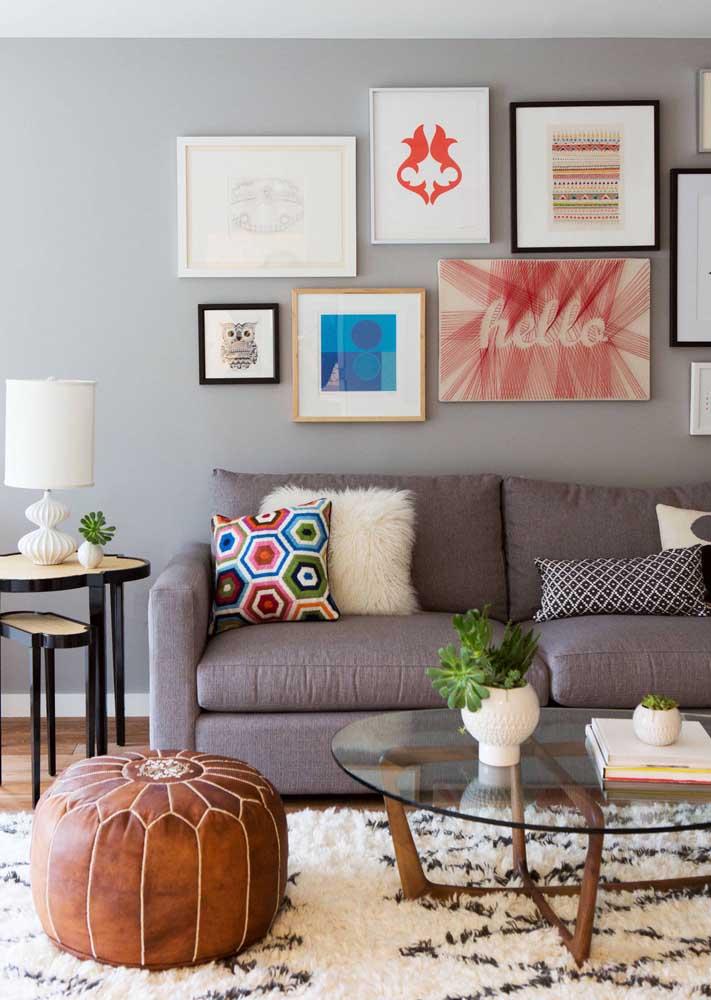 Quadro em String Art com linhas vermelhas em meio a outros quadros tracionais na sala de estar