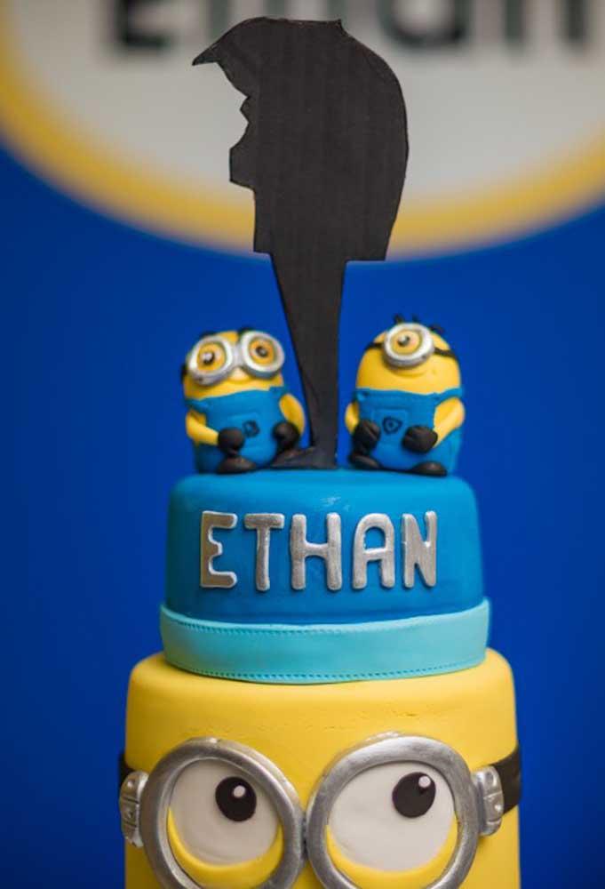 Para fazer um bolo com o tema Minions, o mais indicado é usar um bolo fake. No topo coloque os personagens principais do filme.