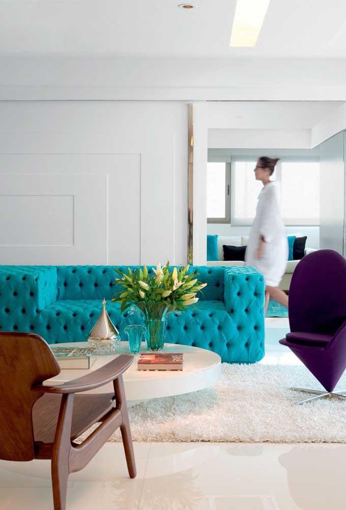 Sofá azul turquesa com acabamento capitonê para a sala de estar contemporânea com paredes brancas e peças em madeira; o grande destaque do ambiente