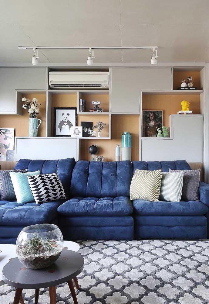 Sofá azul marinho em veludo com almofadas coloridas; destaque para o modelo reclinável e retrátil super confortável