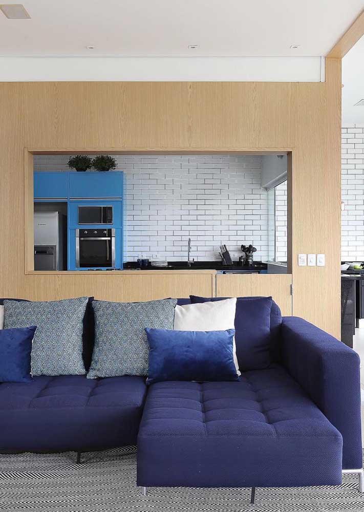 Sofá azul marinho retrátil com assento em capitonê e almofadas brancas e azuis