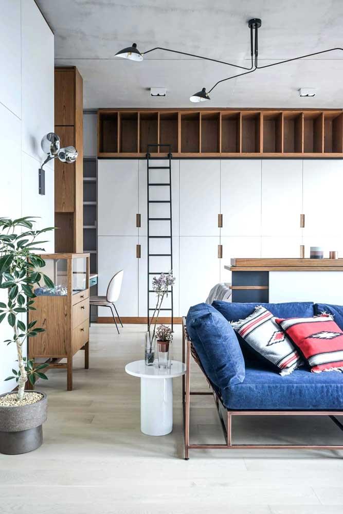 A sala de estar integrada e contemporânea ganhou companhia do sofá azul em veludo com almofadas vermelhas