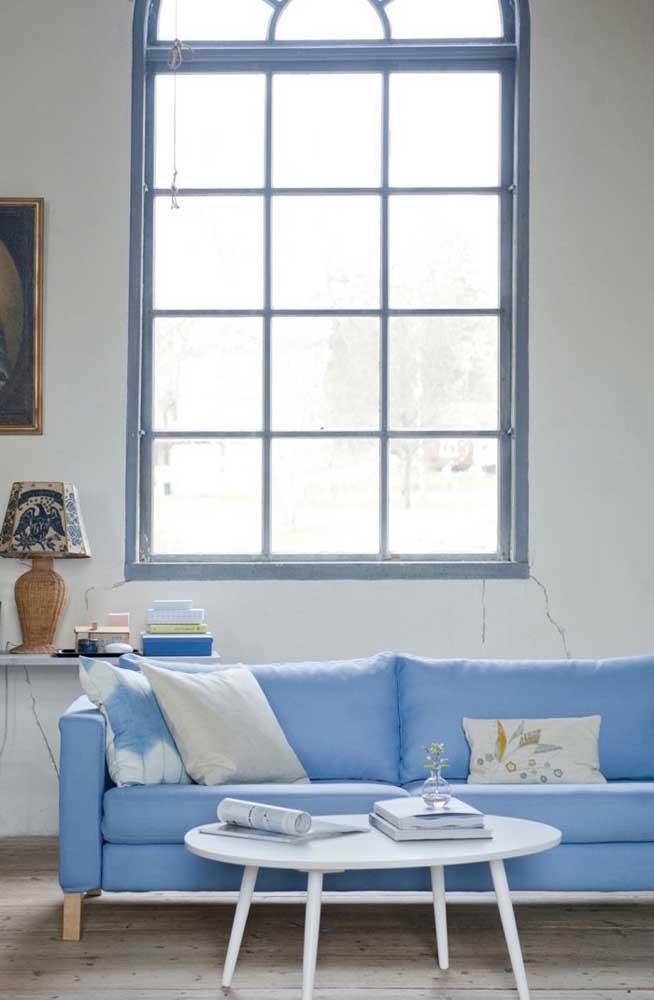 Sofá azul claro de quatro lugares, ornando com a paleta de cores da sala de estar