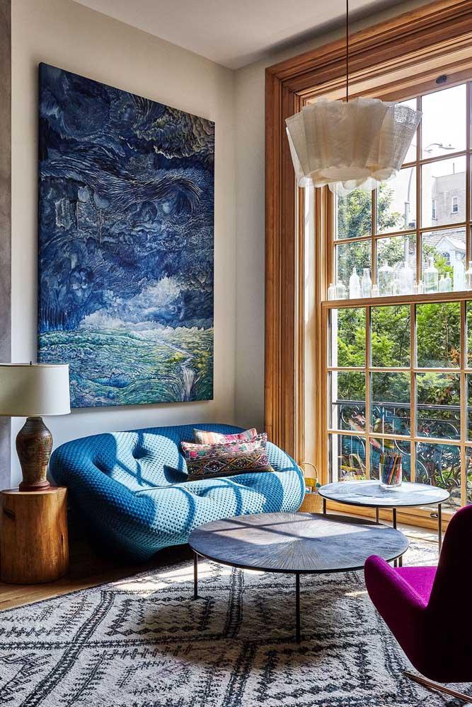 Sofá azul em estilo contemporâneo contracenando com a luz natural da sala de estar