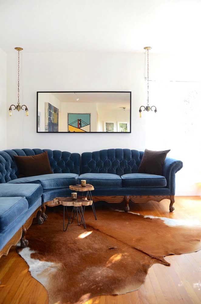 Um elegante e clássico sofá de canto azul petróleo com encosto em capitonê para a sala de estar
