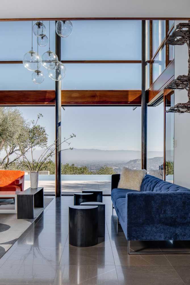 A sala de estar integrada contou com muita entrada de luz natural, favorecendo a presença do sofá azul marinho