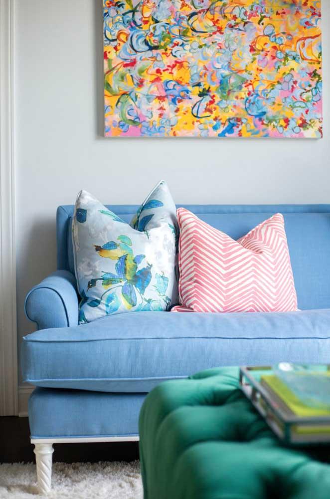 Sofá azul claro com almofadas estampadas para sala de estar colorida
