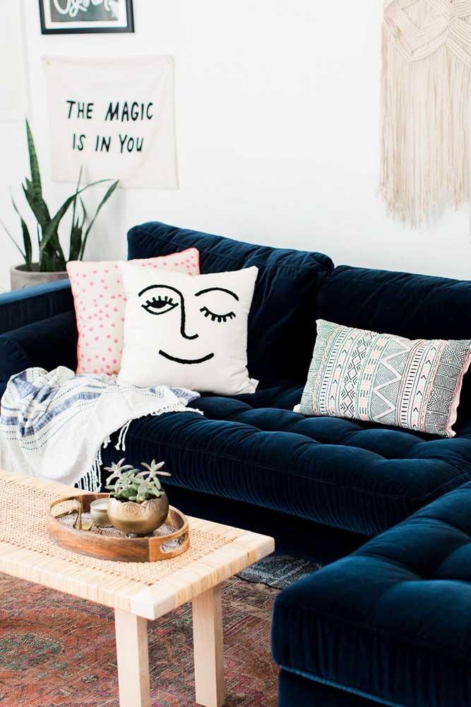 O sofá de veludo azul petróleo recebeu bem as almofadas estampadas e descontraídas