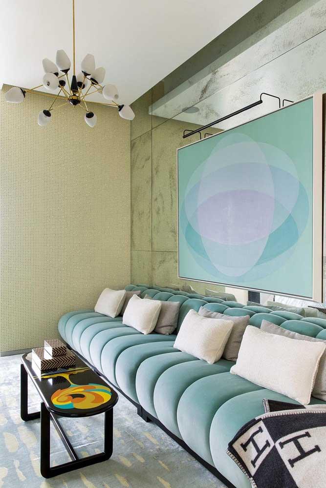 Sala de estar contemporânea com sofá modular azul claro em veludo na mesma tonalidade do quadro na parede