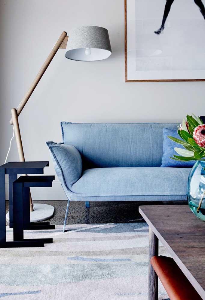 Espaço moderno com sofá azul claro contracenando com a luminária cinza com base em madeira