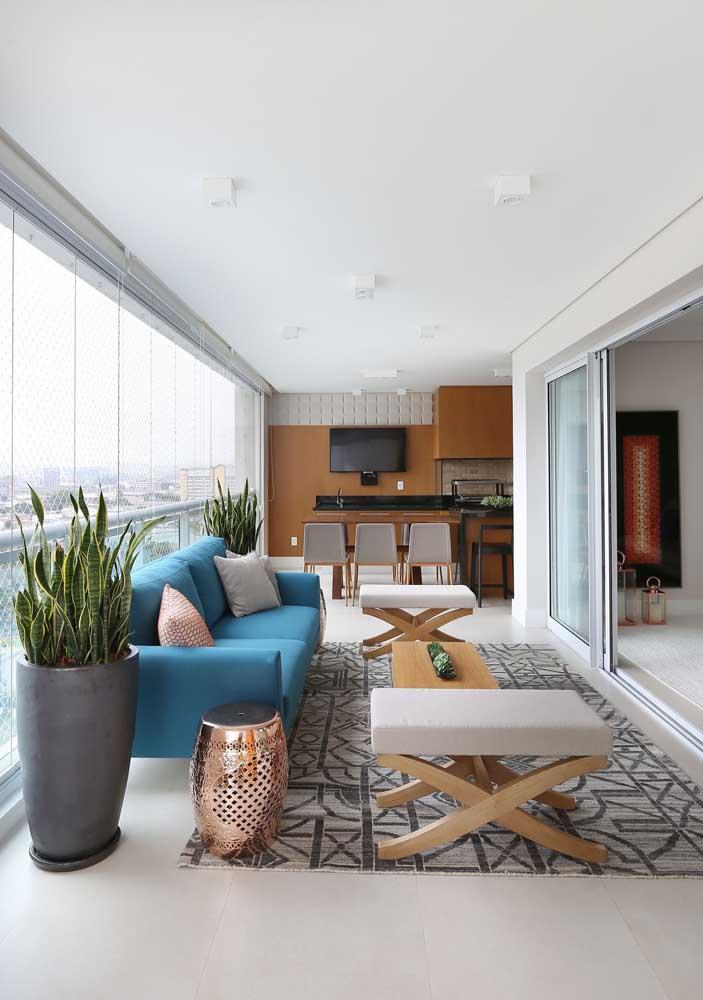Sala de estar integrada com sofá azul combinando com peças contemporâneas