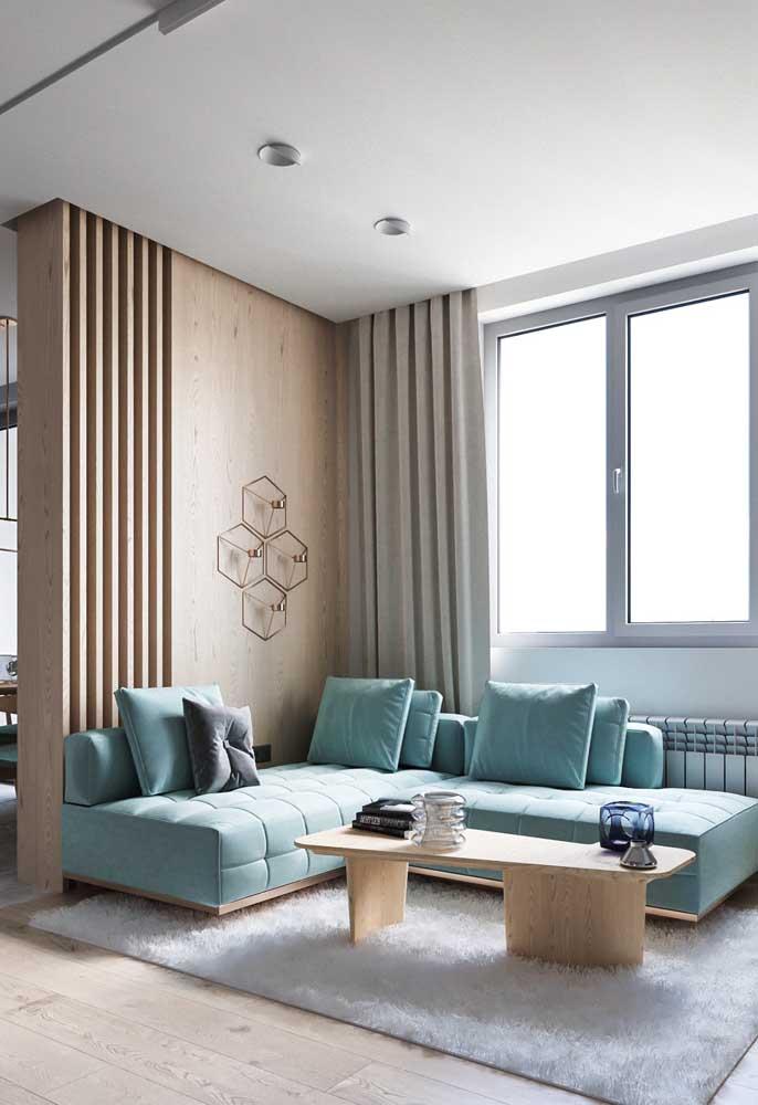 Sofá azul claro de canto com almofadas na mesma tonalidade do tecido; repare que a peça se encaixou perfeitamente na estética clean e neutra do ambiente