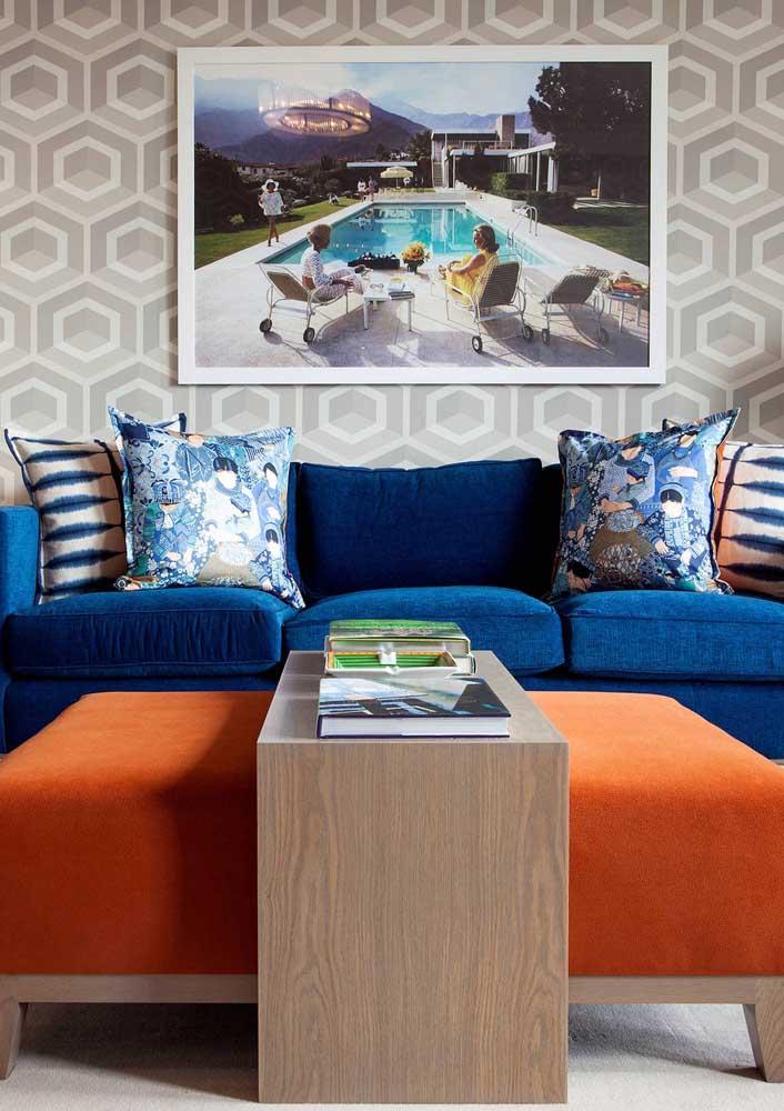 O estilo moderno desta sala de estar recebeu bem o sofá azul escuro com almofadas estampadas e o puff laranja, formando uma perfeita combinação de cores complementares