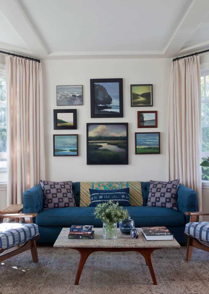 Sala de estar em tons neutros na base com sofá azul royal e almofadas estampadas