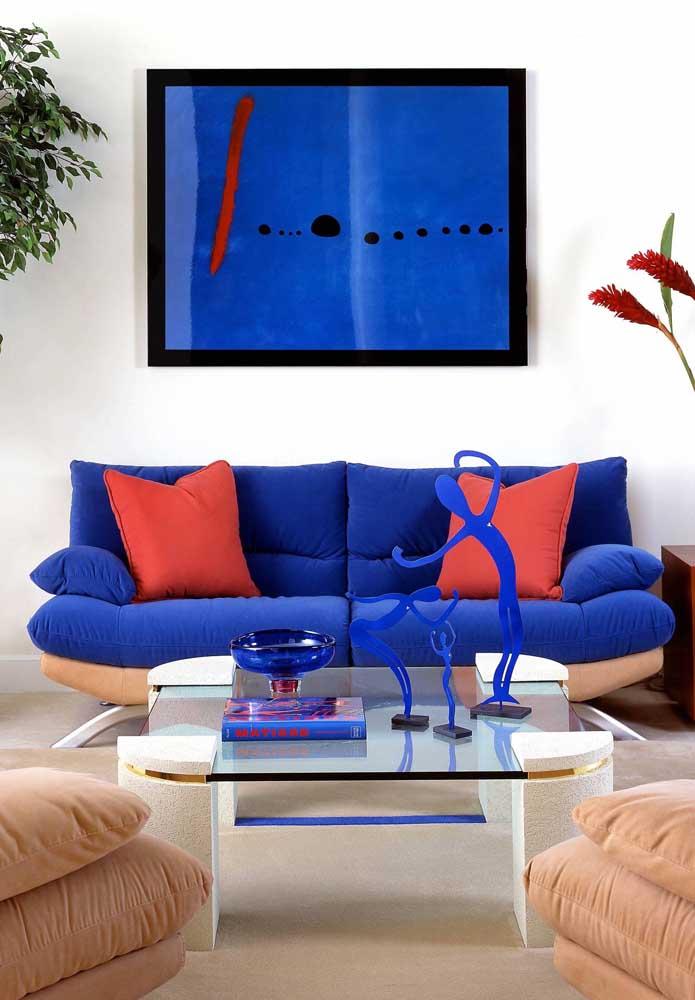 Esse sofá é o destaque da sala de estar; o tom de azul ficou perfeito em contraste com a tonalidade laranja das almofadas, do quadro e das flores