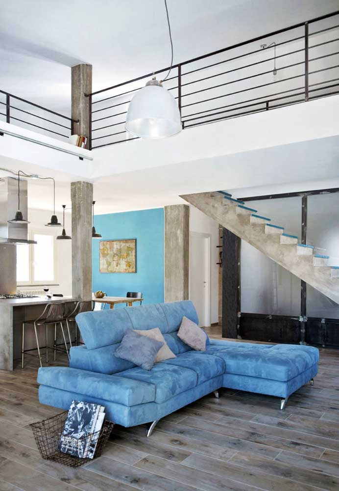 A sala integrada com pé direito alto ficou ainda mais bonita com a presença do sofá azul claro em veludo