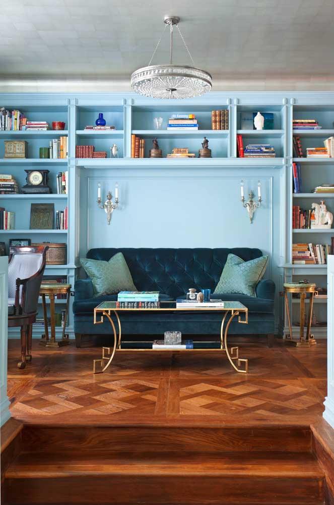 O sofá azul de modelo clássico encaixou como uma luva nessa sala de estar vintage