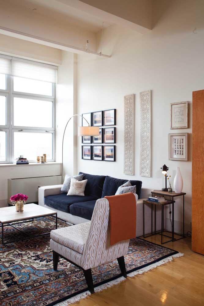 Sala de estar em tons neutros com sofá azul escuro em veludo