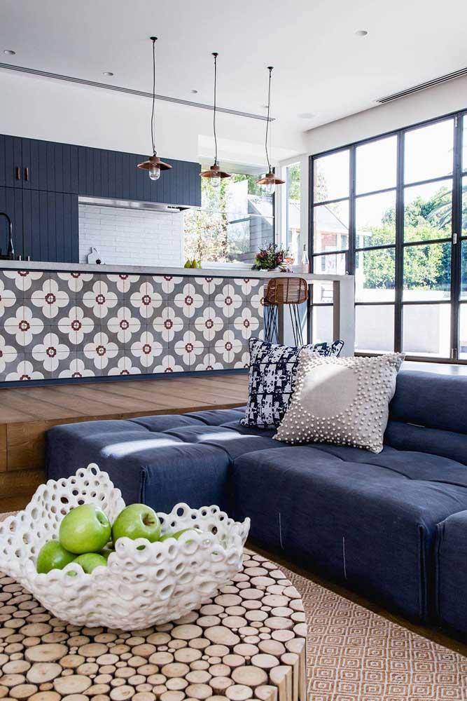 Sofá azul marinho modular para a sala integrada; repare que o tom se repete na cozinha aos fundos