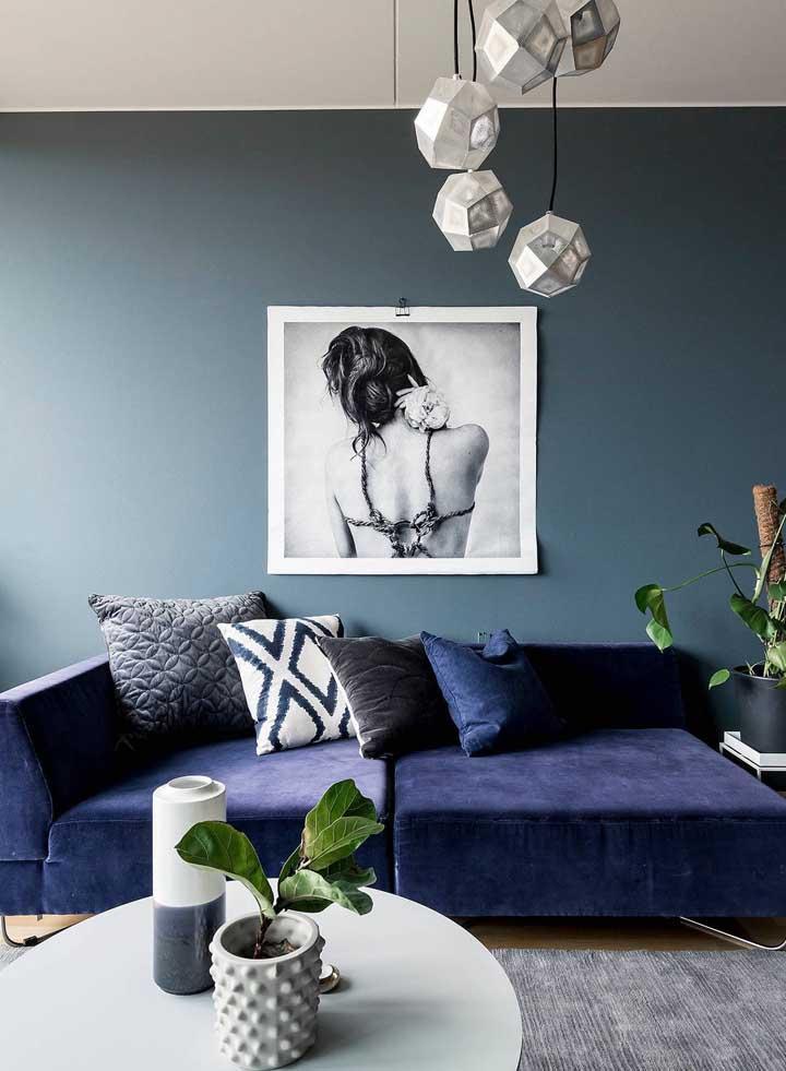 O visual aconchegante desta sala de estar ficou evidenciado com a escolha do sofá azul e das almofadas que o compõe