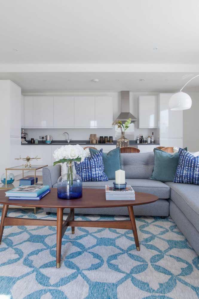 Ambiente clean e muito convidativo com sofá azul claro e almofadas em tons diferentes de azul