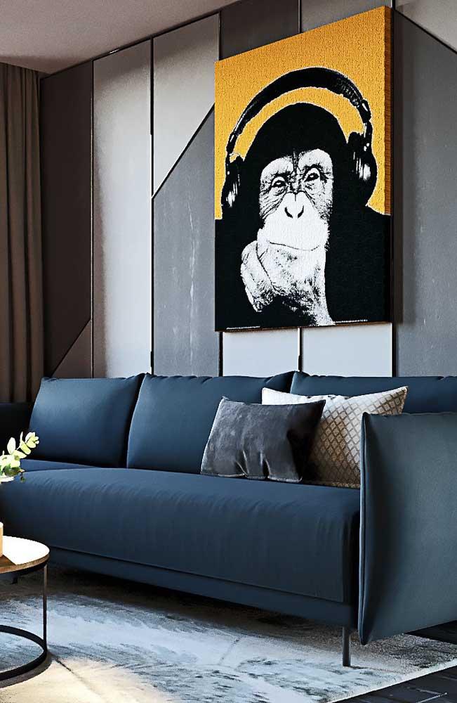 Sofá azul petróleo para a sala de estar moderna; o quadro com detalhes em amarelo forma o contraponto ideal