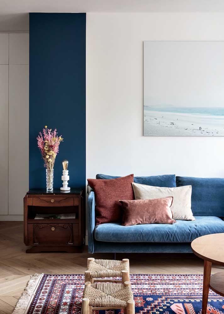 O sofá azul complementou os demais tons de azul que compõe a sala