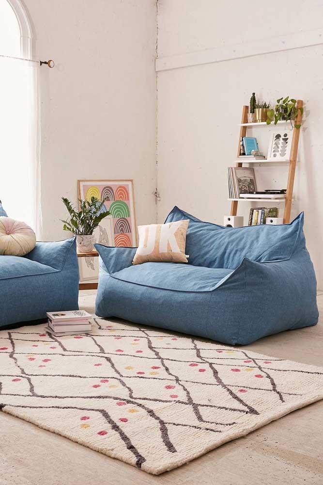 Sala de estar neutra em estilo boho com um sofá azul jeans pra lá de confortável