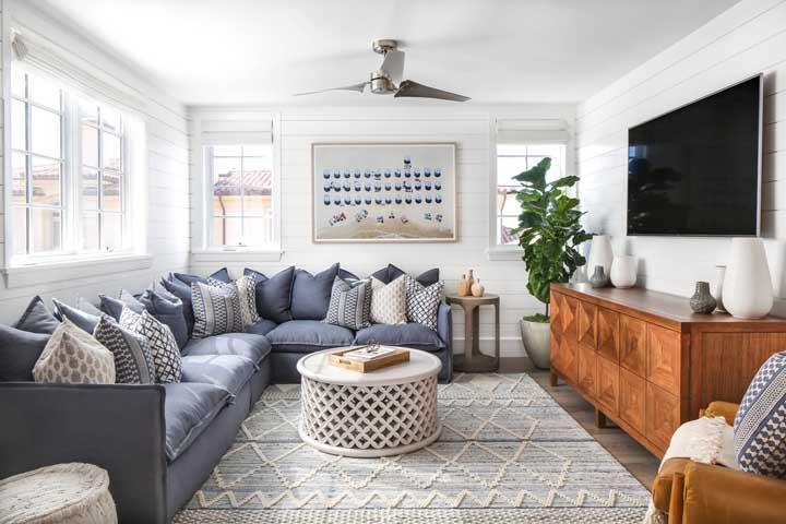 O sofá de canto azul acinzentado otimiza o espaço da sala de estar