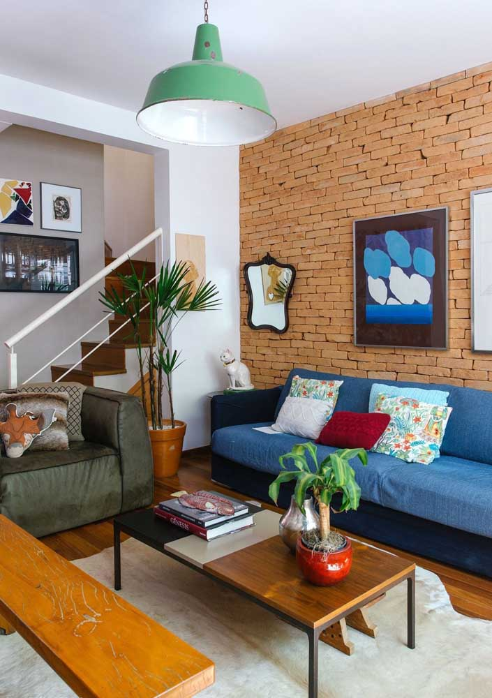 Sofá azul royal para combinar com a parede de tijolos da sala