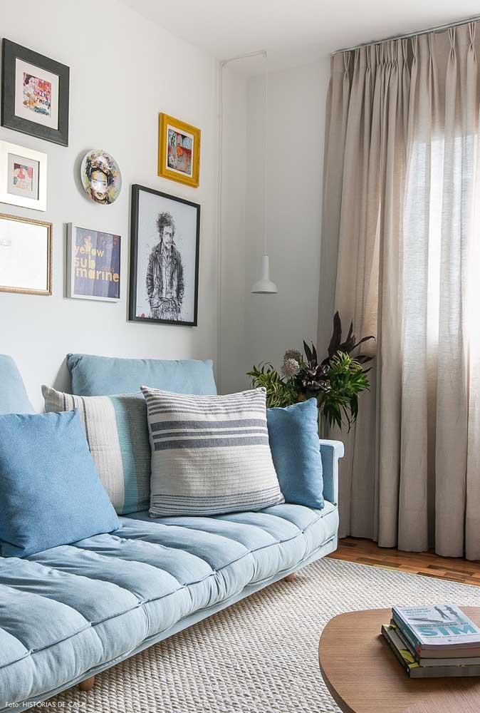 Almofadas em tons neutros fizeram companhia para este sofá azul claro