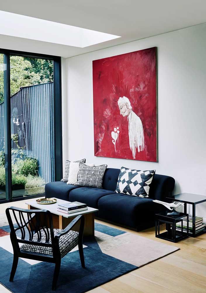 Sofá azul marinho modular com almofadas estampadas; repare que o tapete segue na mesma tonalidade do sofá, enquanto o quadro na parede traz uma cor complementar