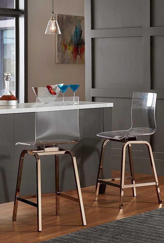 Cozinha americana com cadeiras de acrílico em estilo banqueta; destaque para a base em tom de cobre rosé