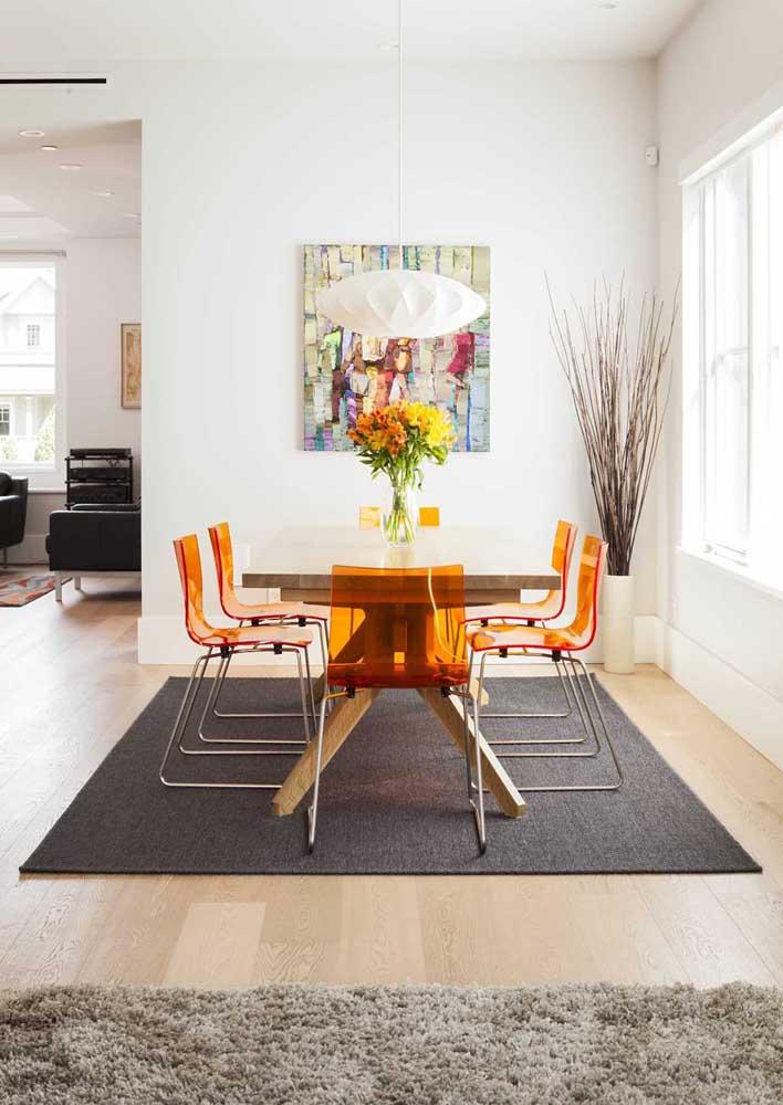 Um pouco de cor não faz mal a ninguém! A proposta aqui foi usar cadeiras de acrílico laranja com base metálica em torno da mesa de jantar