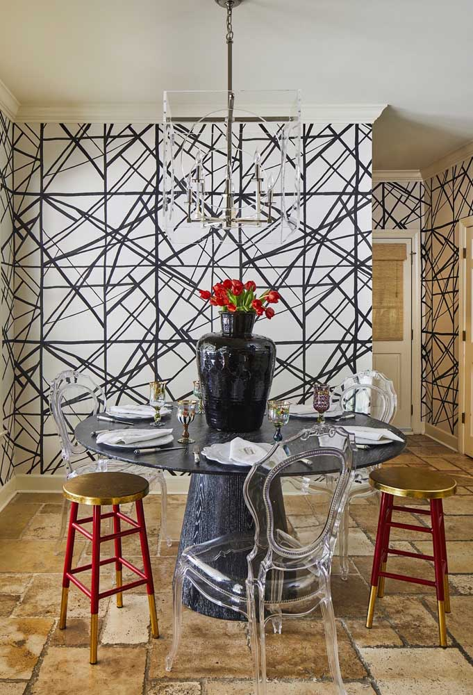 Composição marcante e cheia de personalidade nessa sala de jantar: a mesa redonda reúne cadeiras de acrílico com banquetas em tom de dourado