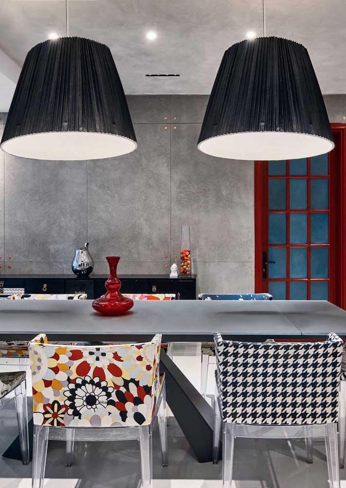 Capas em cores e estampas diferentes para cada uma das cadeiras de acrílico dessa sala de jantar
