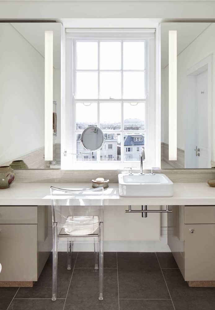 No banheiro, a cadeira de acrílico acompanha a bancada servindo de apoio para o momento da maquiagem