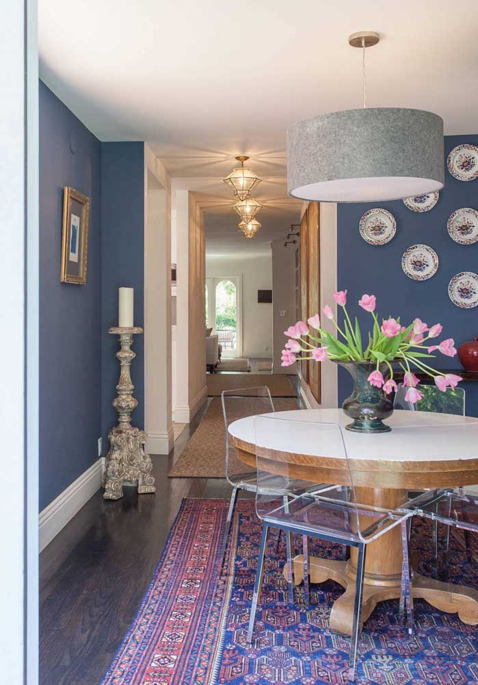 A sala de jantar super bem decorada apostou no uso de cadeiras de acrílico, trazendo uma leveza e neutralidade ideais para o ambiente que já abusa de cores e texturas em outros objetos