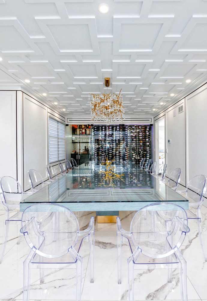 Mesa ampla toda rodeada por cadeiras de acrílico transparente; é bom lembrar que um projeto assim, no entanto, pode sair pesado para o bolso