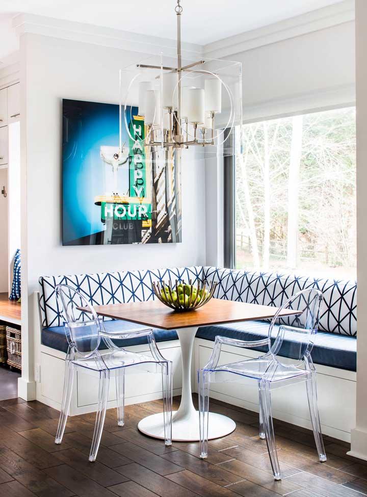 Canto alemão em tons de azul e branco com duas cadeiras de acrílico transparente; repare que as cadeiras conversam muito bem com a luminária também transparente