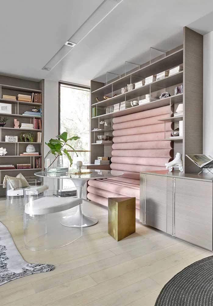 A sala de jantar em tons neutros e delicados traz cadeiras de acrílico transparente em estilo poltrona