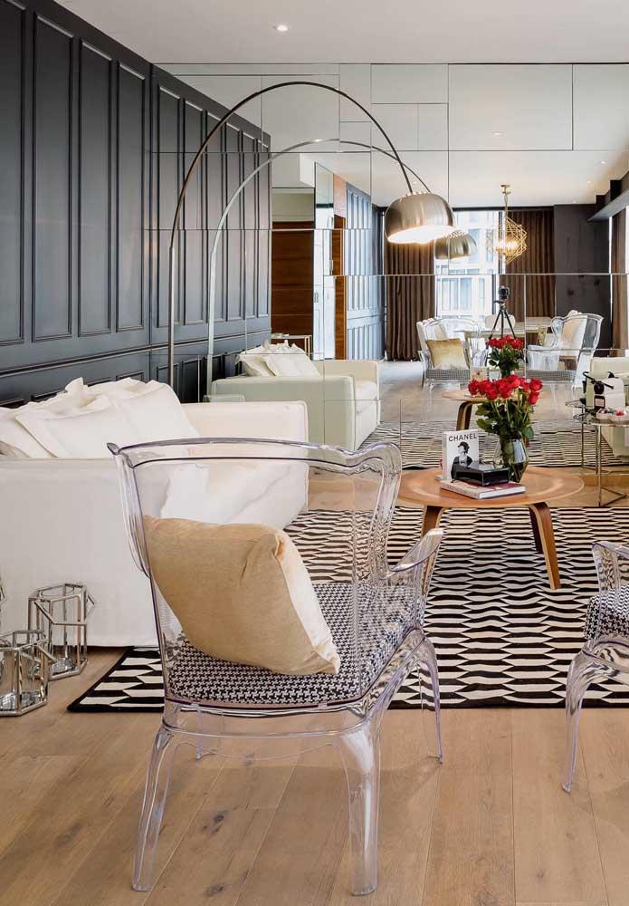 Nessa sala, as cadeiras de acrílico e o espelho na parede dão o tom da decoração