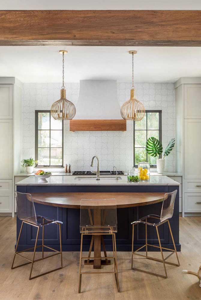 Nessa cozinha gourmet, a inusitada mesa em meia lua acompanha cadeiras altas de acrílico com base em tom de cobre