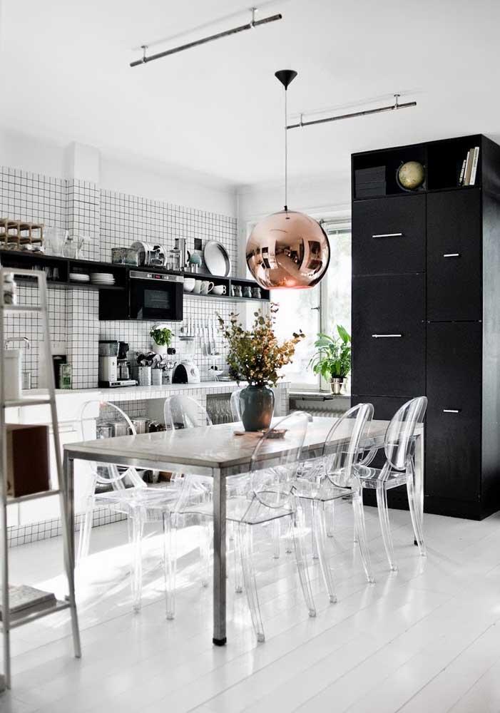 Cozinha e sala de jantar integradas com destaque para a mesa de inox acompanhada de cadeiras de acrílico transparente